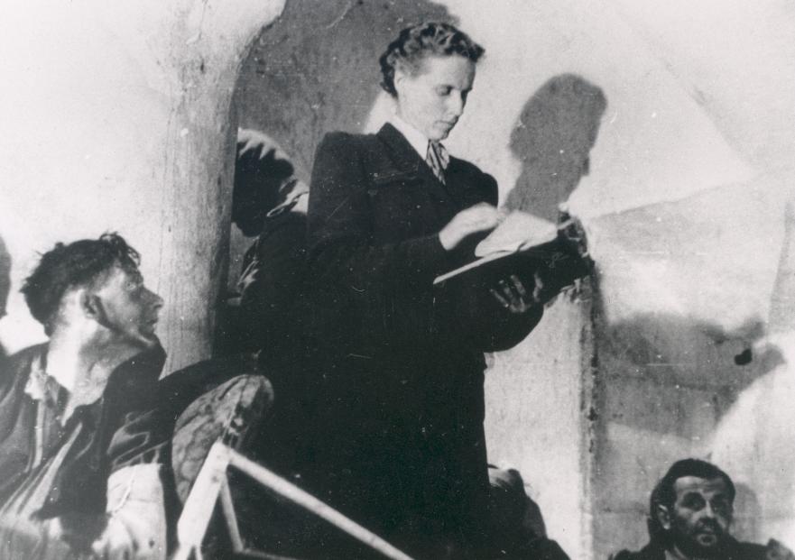 Voorlezen Psalm 91 aan de gewonde Britse militairen tijdens de Slag om Arnhem; Kate ter Horst bij opname film Theirs is the Glory, uit 1946. (foto collectie Airborne Museum)